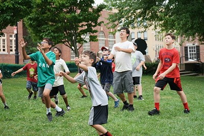 Summer campers at the Tsongas Industrial History Center play outdoor games in Boardinghouse Park