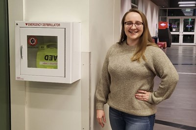 Honors biology major Katie Moreland by a defibrillator in University Suites