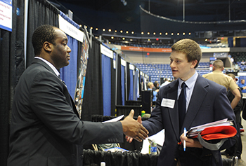 David Chieh III, left, a Verizon corporate recruiter and 2012 alumnus, greets Jonathan Campelli '14 at the Fall Career Fair.