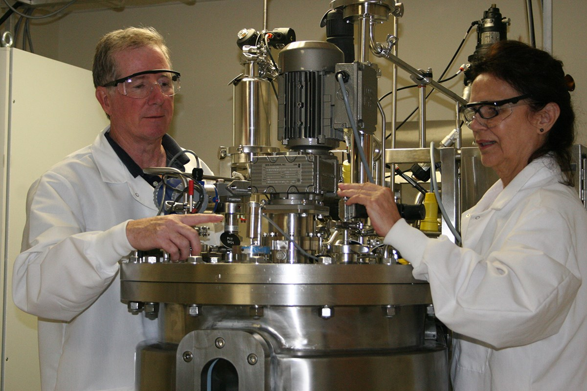 Assoc. Prof. Carl Lawton and a researcher use the bioreactor at the Massachusetts Biomanufacturing Center at UMass Lowell