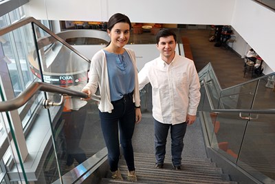 Jessica and Jack Carroll stand on the stairs in the business school