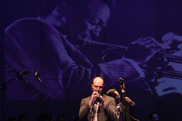 Garrett Michaelsen blows trumpet beneath a projection of Miles Davis, and bassist Charles Gabriel leans into the rhythm during a jazz set.