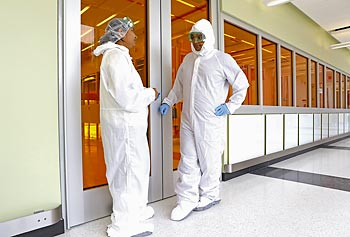 Researchers working in the clean room of the Emerging Technologies and Innovation Center (ETIC) wear protective gear to help contain particles that might otherwise contaminate the lab areas.