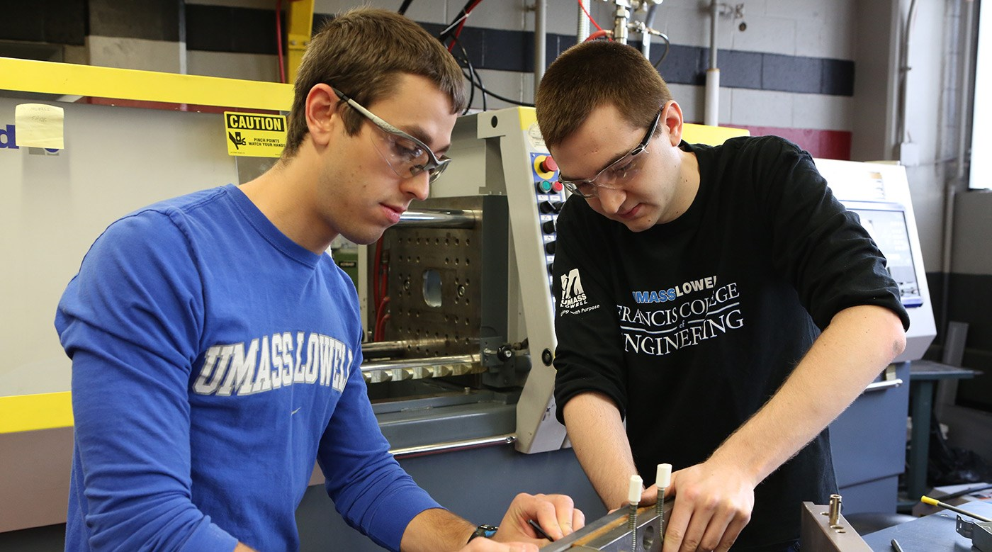 Two male engineering students working on equipment at their co-op.