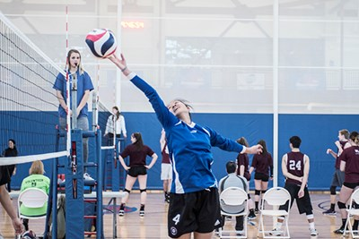 a volleyball player taps the ball over the net