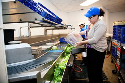 A dining hall worker dumps scrap lettuce into a chute to be composted