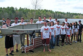 "UMass Lowell's 2012 concrete canoe team poses with the ""Revolution."""