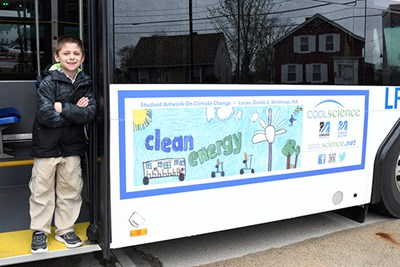 One of the winners of the 2019 Cool Science poster contest poses on a Lowell Regional Transit Authority bus displaying his artwork.
