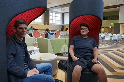 Students sit in designer chairs at the marketplace