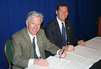 UMass Lowell Chancellor Marty Meehan, left, and Middlesex County District Attorney Gerard Leone sign a partnership agreement for research and intervention programs.