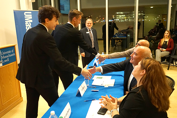 Freshmen Greg Montemurro, left, and Dave Seybert shake hands with the judges after winning the DifferenceMaker DCU Innovation Contest.