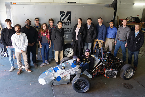 River Hawk Racing president Kevin Nguyen and Collegiate DECA chief marketing officer Kelly Foley, center, are flanked by engineering and business students who are collaborating on a race car for a Formula SAE competition in June in Lincoln, Neb.