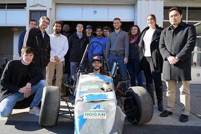 Business and engineering students pose with the River Hawk Racing car from 2017 competition