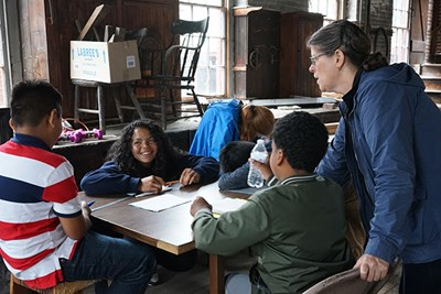 Rising Loaves director Mary Guerrero and small group leader Lidyanette Gonzalez work with students in the carpenter shop.