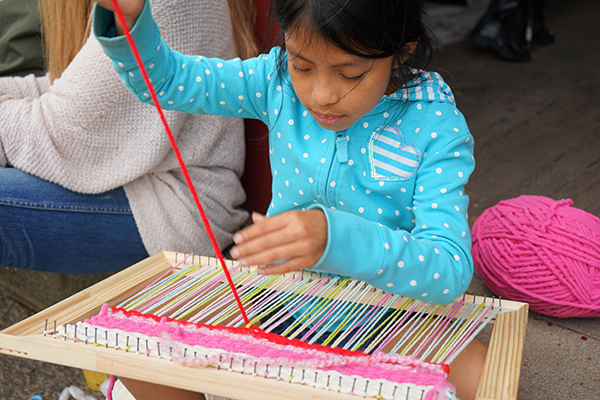 "Jennifer Merida works on her weaving during ""Choice"" time at the Rising Loaves camp."