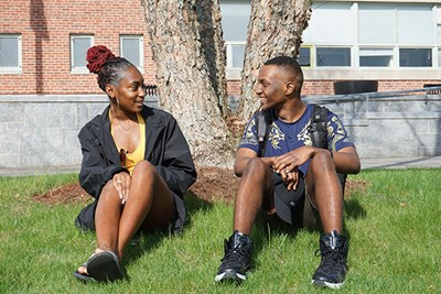 First-year UMass Lowell students Nicquela Roach (left) and Corey Sanon chat after class