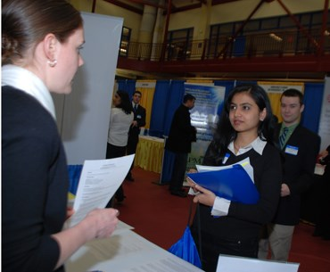 A female student observing and listening to a lady giving a talk about her booth at a career fair.