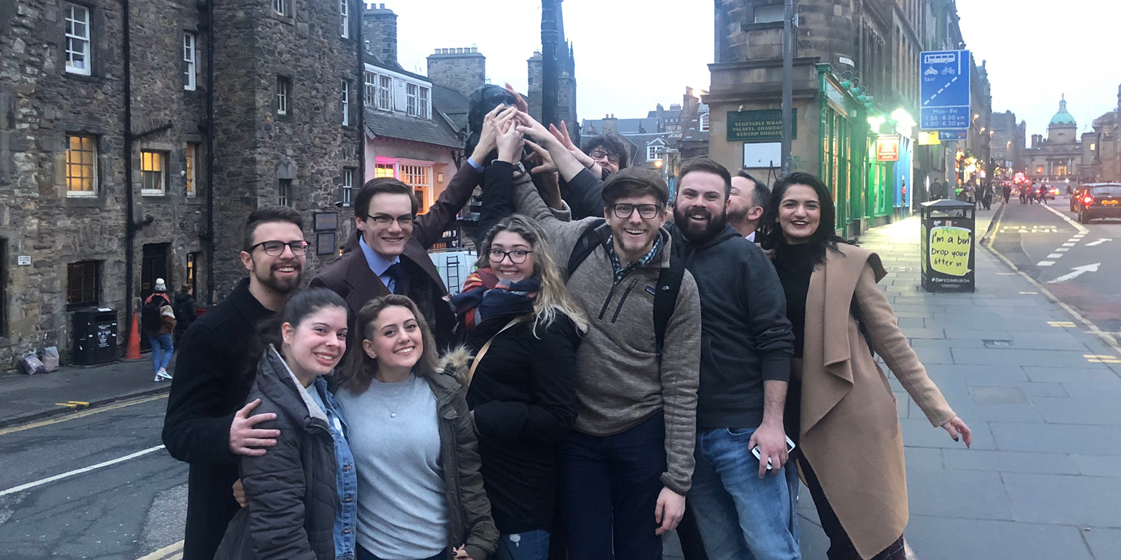 Dana Ibrahim, second from left in front, and fellow students touch a statue on street in Edinburgh, Scotland.