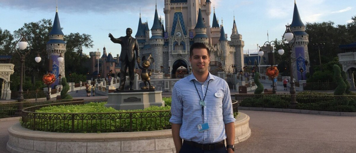Dean Kennedy standing in front of the Magic Kingdom at Disney World