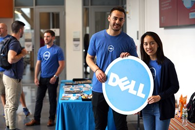 Business grad Mai Pham and engineering alum Nabil Saleh hold a Dell sign in the Pulichino Tong atrium