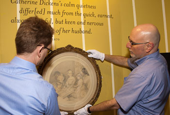 "Florian Schweizer, left, and David Blackburn installed the long-awaited portrait of Charles Dickens's young children for the ""Dickens in Massachusetts"" exhibit running through October."
