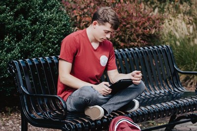 A student reads from a tablet while sitting on a bench