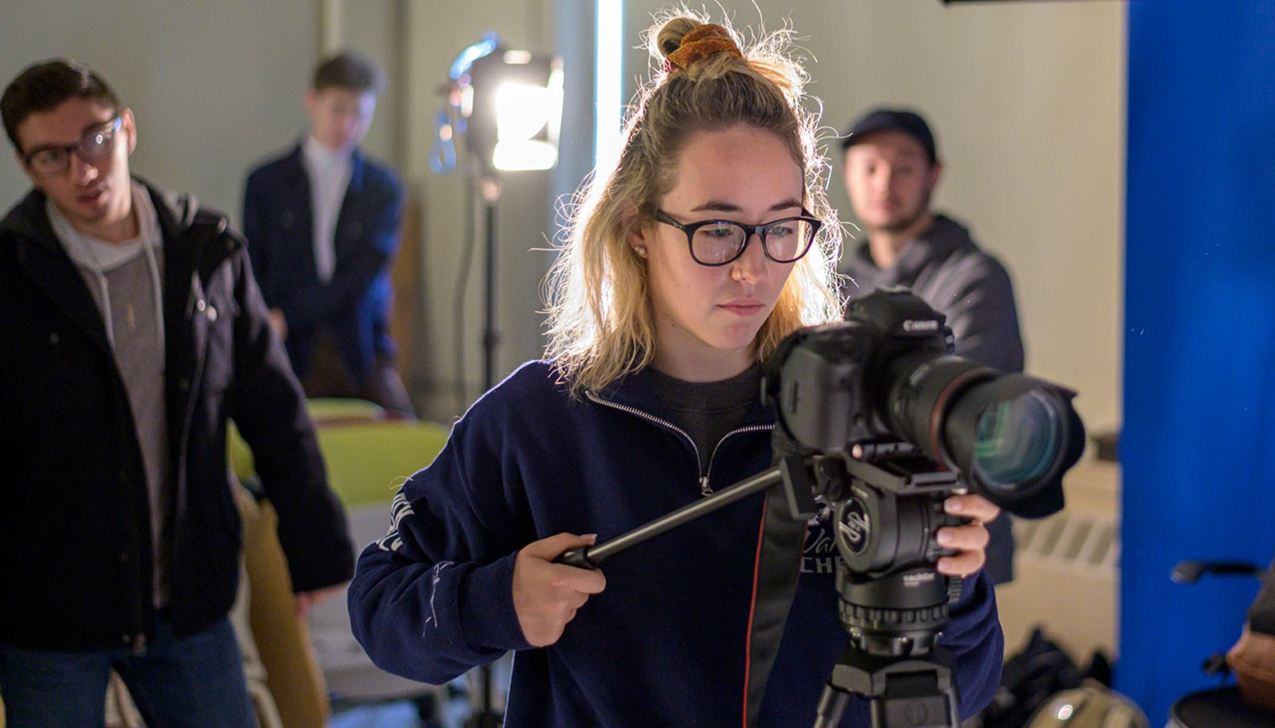 Digital Media student operating a video camera in a UMass Lowell studio