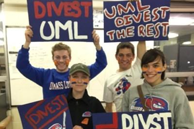 Climate Change Coalition members hold posters before a hockey game