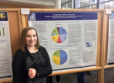 Student Meaghan O'Brien stands in front of her research poster