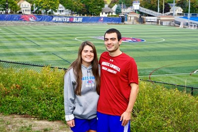 Siblings Abby and Ben Drezek stand in front of the UML soccer pitch