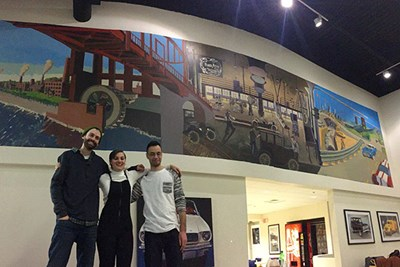 Art students pose in front of their mural at Drum Hill Ford