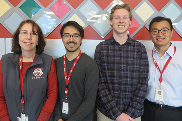 Executives Lynne Garone, left, and Simon Nip, right, with co-op students Robert Rosario and Daniel Magee in front of a color-changing display in E Ink's lobby.