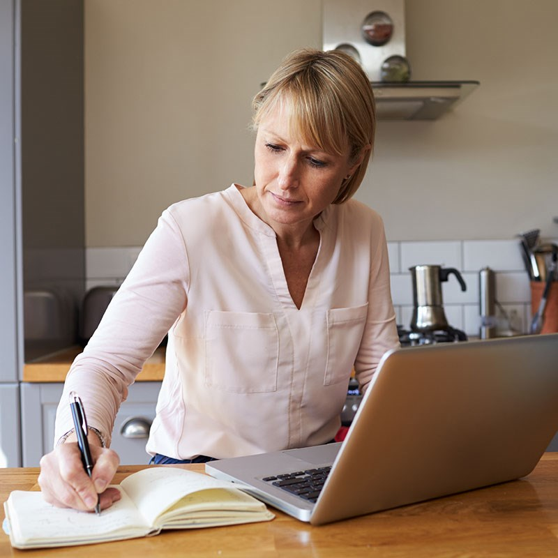 Woman seated at kitchen counter jots in notebook in front of laptop
