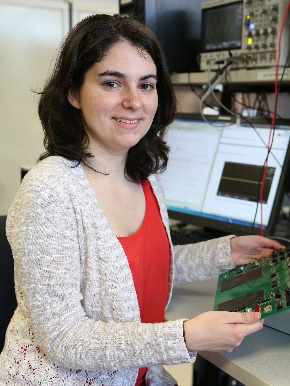 ECE student, Erin Graceffa poses with electrical equipment and holding a circuit.