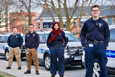Four student EMTs stand by their vehicles on East Campus