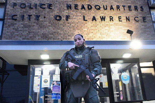 Jessica Botero, the first female members of the Lawrence Policy Department's Emergency Response Team, stands outside the police station.