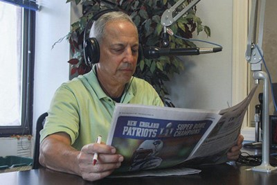 Man reading newspaper into microphone