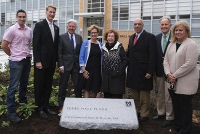 Eight people stand in front of Perry Hall Plaza stone