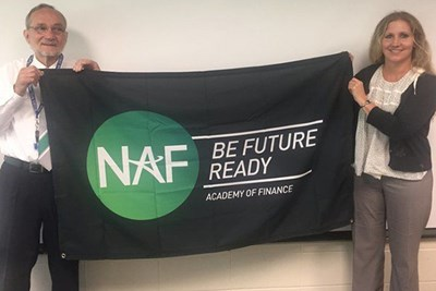 Fred Press and Lori Capra unveil a banner announcing the new NAF Academy of Finance at Haverhill High.