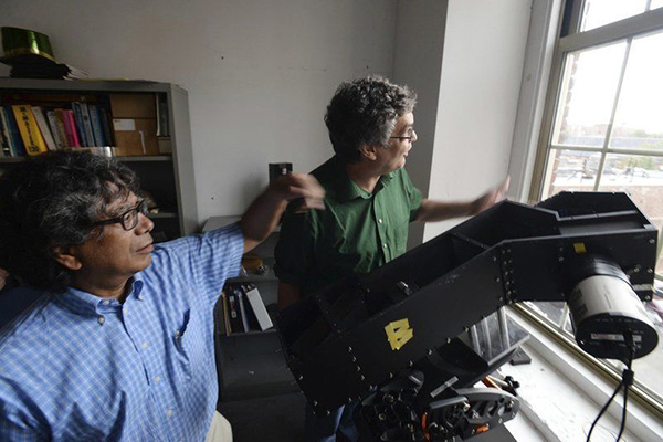 UMass Lowell physics professors Tim Cook, left, and Supriya Chakrabarti work on equipment they will use to conduct experiments during the upcoming solar eclipse.Paul Bilodeau