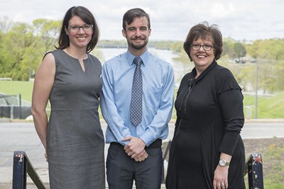 Liam Fouhy, center poses with professor Sabrina Noel Feldeisen, left, and Lawrence Senior Center Executive Director Martha Velez.