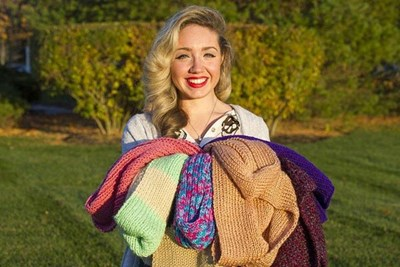 Ashley Bolis, founder of Project Warm & Fuzzy, poses with scarves she has collected so far this year. Eagle-Tribune photo by Amanda Sabga