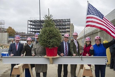 State Rep. Brian Dempsey, UMass Lowell Chancellor Jacqueline Moloney, Mayor James Fiorentini, Ron Trembly, Bill Grogan, Sally Cerasuolo-O'Rorke and Lisa Alberghini sign a beam during a topping off ceremony at Harbor Place.