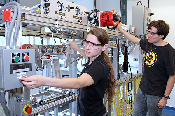Nanomanufacturing Center postdoctoral researcher Erin Keaney and plastics engineering senior Stephen Burbine work with the center's continuous, roll-to-roll flexible substrate printer at the Saab Emerging Technologies and Innovation Center on North Campus.