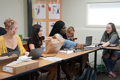 UML education majors open Chromebooks they were given as part of a pilot project