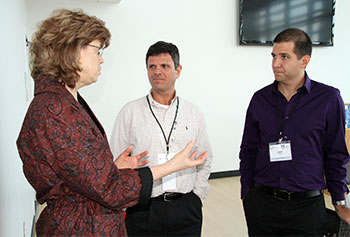 Edwin Garro MS '92, center, speaks to Manning School of Business Dean Kathy Carter during a recent visit to campus.