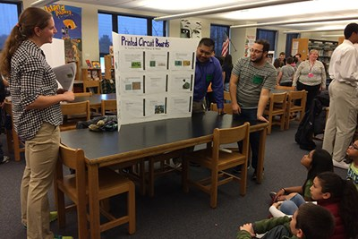 Mechanical engineering students Courtney Britko, David Chhuon and Alli Ramadan explain printed circuit boards to fifth-graders at Sullivan Middle School.