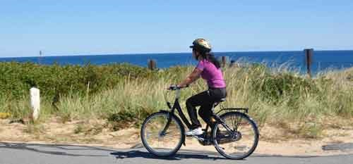 "A female student riding a bike provided by the ""free wheeler's"" program near a cape."
