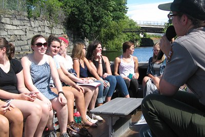 Students in the First-Year Seminar in Honors take a canal boat tour with a Lowell National Historical Park ranger
