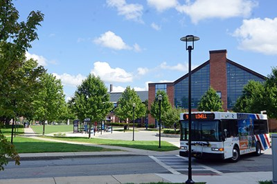 A city bus leaves the traffic circle in front of the Campus Rec Center